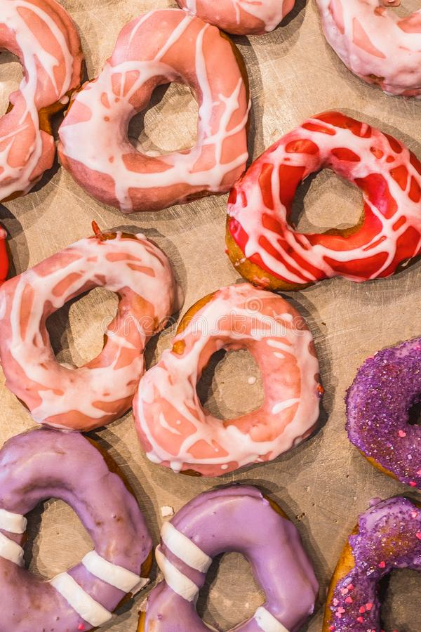 Valentines Day Donuts Full of Color. Assorted color and shapes of delicious donuts on a tray for Valentine`s Day stock image