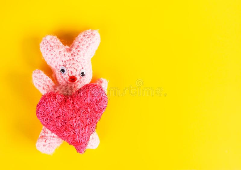 Valentines Day card with crocheted handmade toy bunny and decorative heart. Valentines Day festive card with crocheted handmade toy bunny and decorative heart stock photography