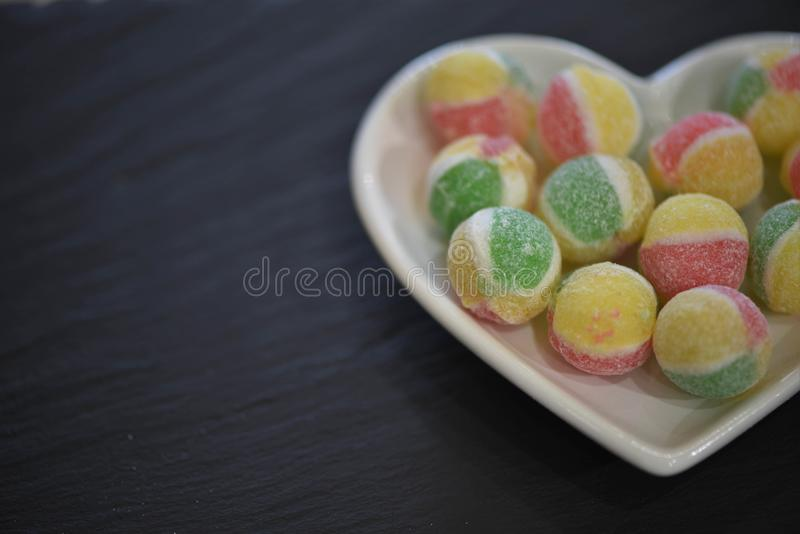 Food photography for Valentines with a white love heart shape dish filled with candy sugar sweets in green yellow and red colors. Valentines day food photography royalty free stock photos