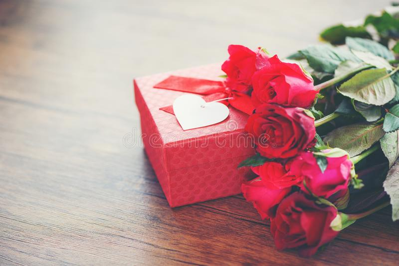 Valentines day gift box flower love concept Red gift box with ribbon bow red roses flower on wooden table royalty free stock images