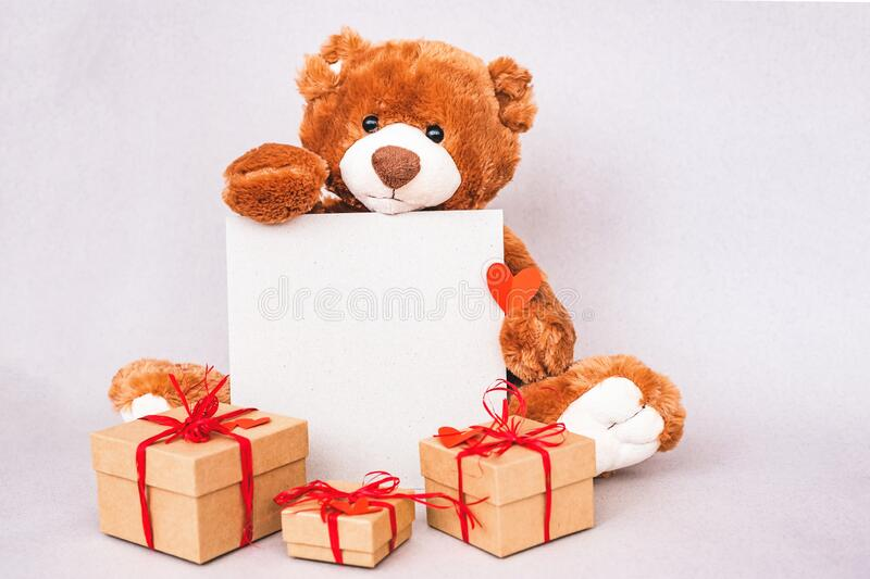 Valentines Day Teddy bear holding place for text, red heart and gift box. Retro romantic style. Creative greeting card stock photography