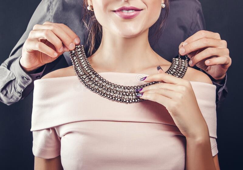 Valentines day gift. Man helping his girlfriend to try on gem necklace. Romantic present for holiday. Love couple. Celebrating royalty free stock photography