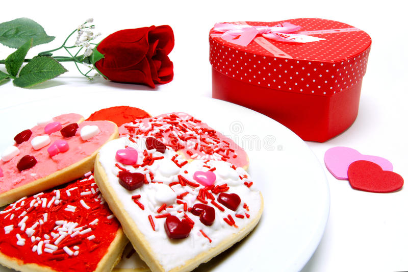 Valentines Day gifts. Colorful Valentines Day cookies on a plate with gift box and rose royalty free stock image