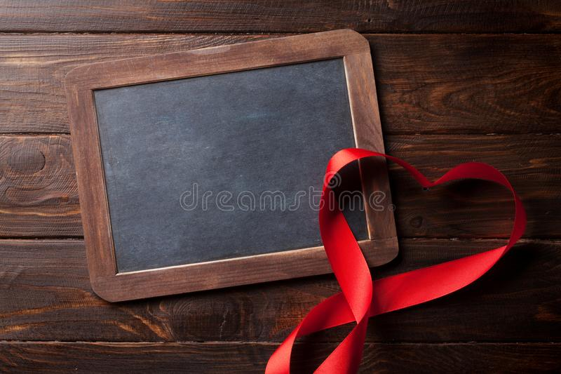 Valentines day greeting card with heart ribbon. Valentines day greeting card with red heart ribbon on wooden table. With chalkboard for your greetings stock photo