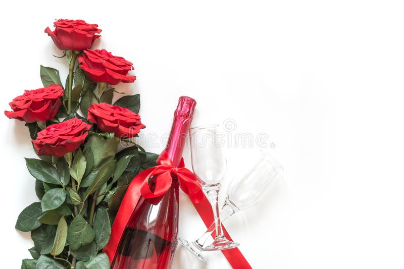 Valentines card with red roses, champagne bottle on white. Top view with space for text. Flat lay royalty free stock image