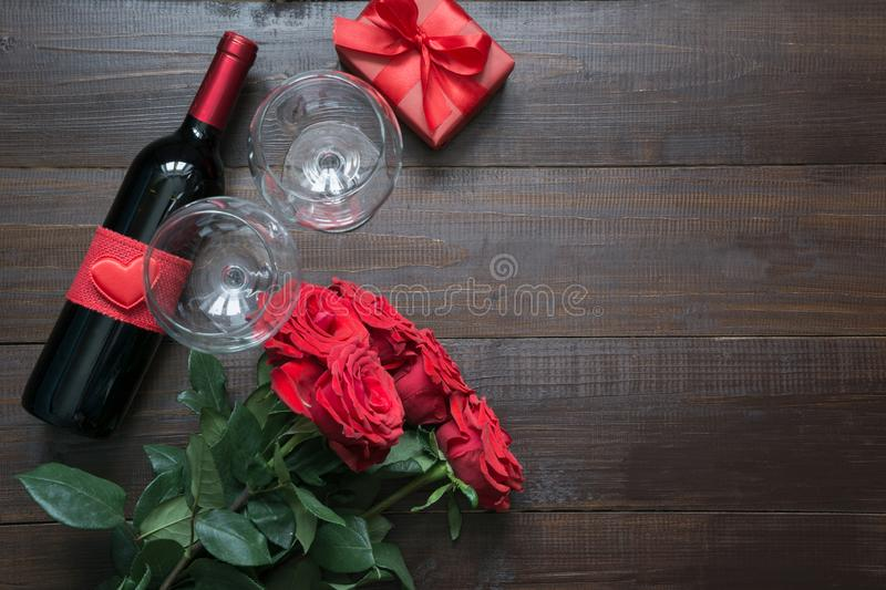Valentines card with romantic red roses, wine bottle, heart and red gift box on wooden table. Top view with space for text. Flat royalty free stock images