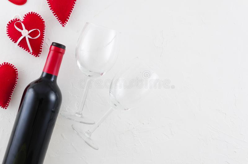 Valentines day greeting card with wine bottle, felt hearts and wineglass on white background. Top view with space for royalty free stock photos