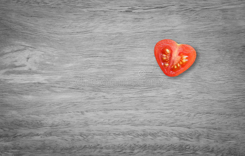 Valentines day. Healthy food with monochrome table wood style. Heart tomato shaped cut in half royalty free stock photography