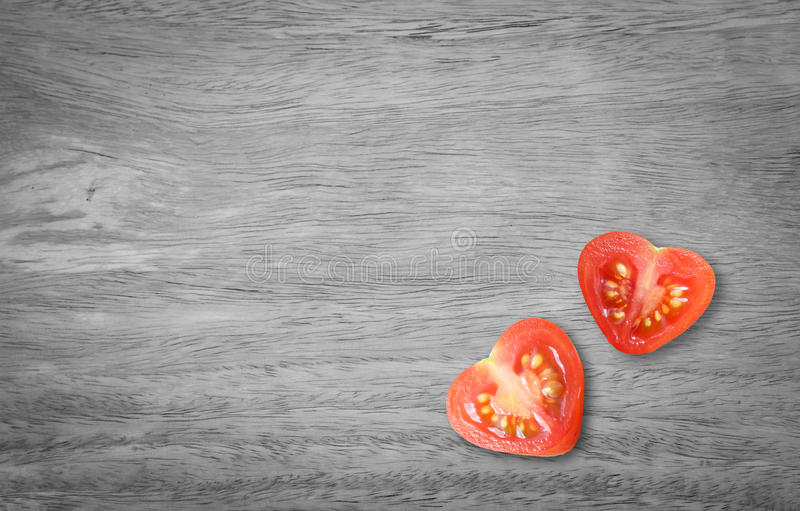 Valentines day. Healthy food with monochrome table wood style. Heart tomato shaped cut in half royalty free stock images