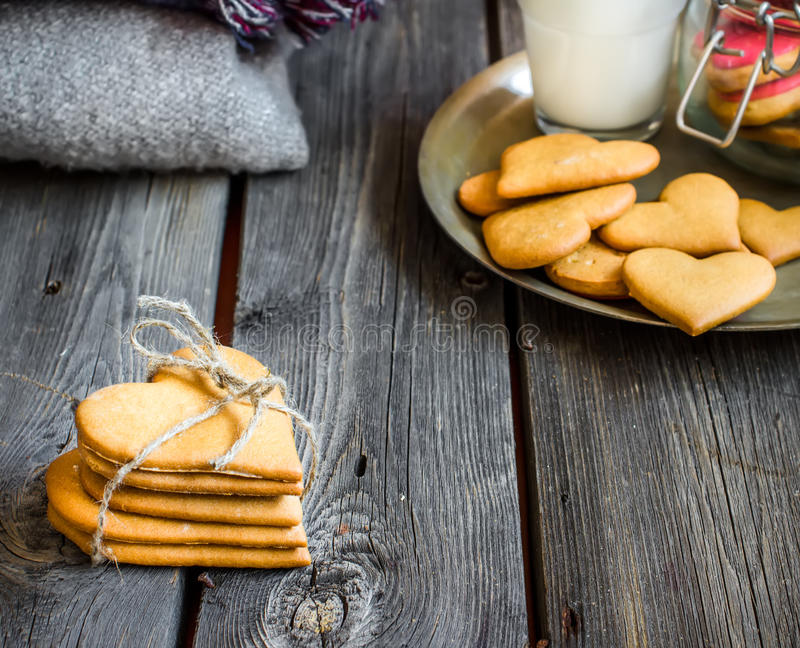 Valentines day heart shaped cookies and glass of milk. Valentines day heart shaped cookies and glass of milk on rustic wooden background. Selective focus royalty free stock photo