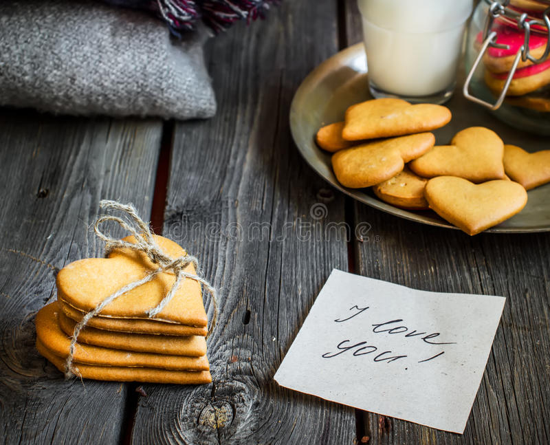 Valentines day heart shaped cookies and glass of milk. Valentines day heart shaped cookies and glass of milk on rustic wooden background. Selective focus royalty free stock image