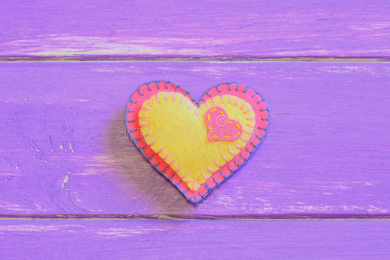 Colorful felt heart on a wooden background with copy space. Valentine background. Happy Valentines symbol. Closeup. Valentines Day heart symbol. Valentine crafts royalty free stock photos