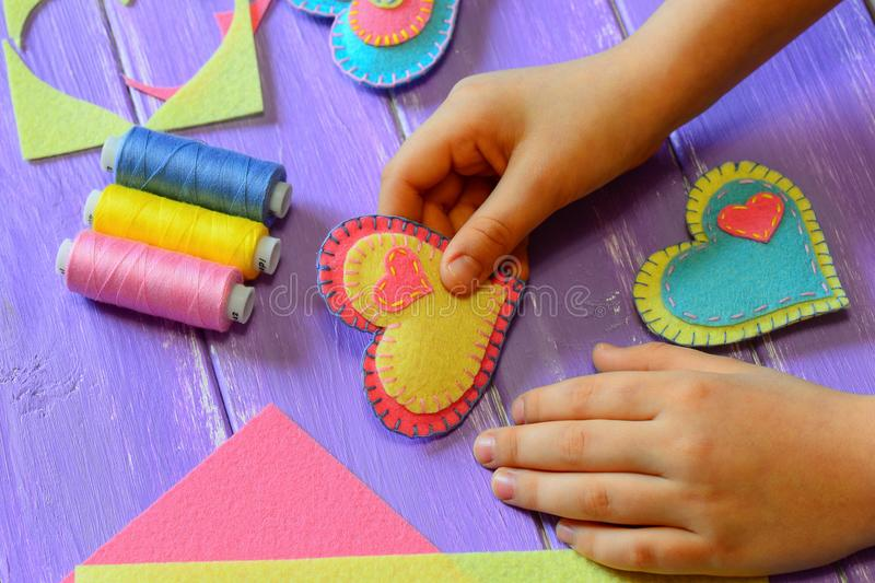 Kid holds a felt heart in his hand. Kid made a felt heart. Colorful felt hearts, scissors, thread on a wooden table. Valentines Day heart symbol. Valentine stock image