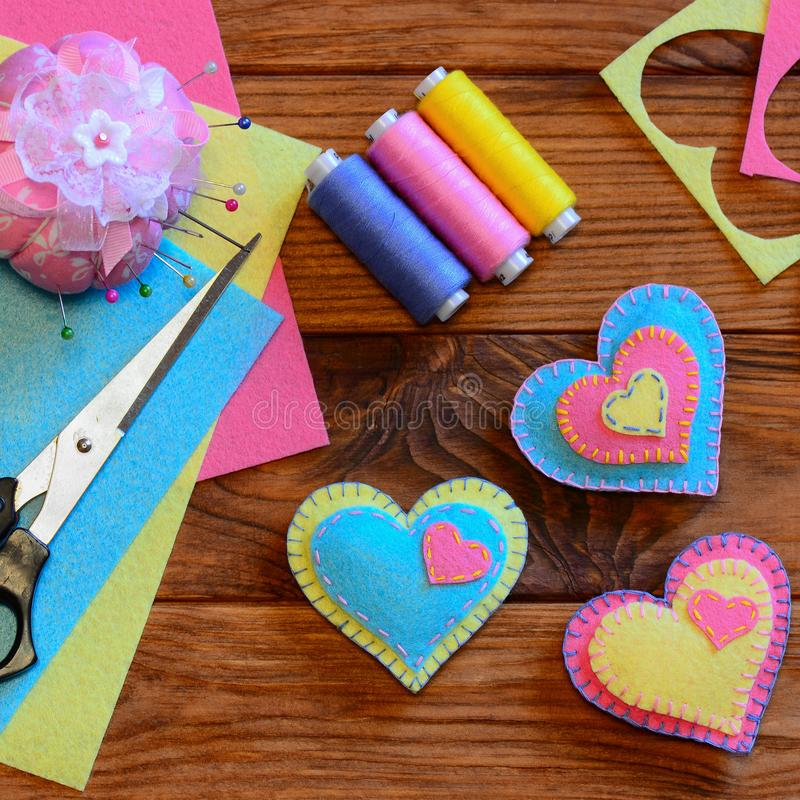 Valentines day hearts. Bright felt heart ornaments, scissors, thread set, pincushion, needles, thimble, felt sheets. Valentine`s Day heart crafts for kids stock images
