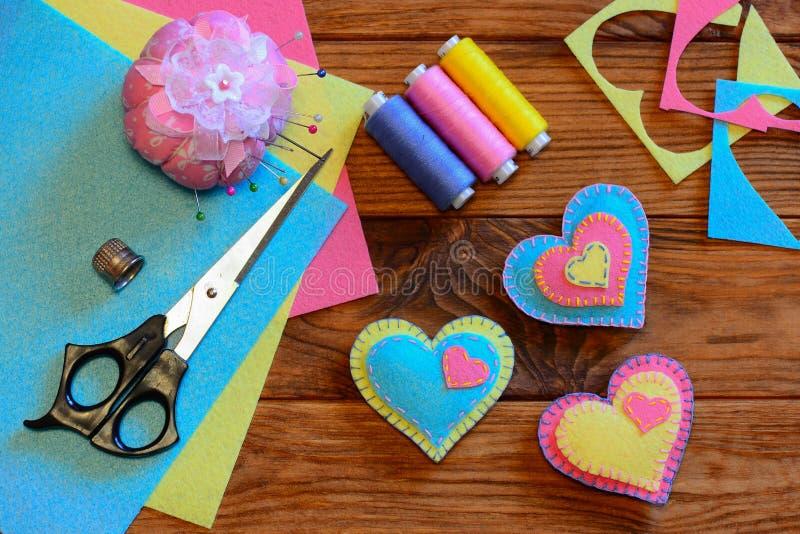 Valentines day hearts ornaments. Colorful felt heart ornaments, scissors, thread set, pincushion, needles, thimble, felt sheets royalty free stock photos