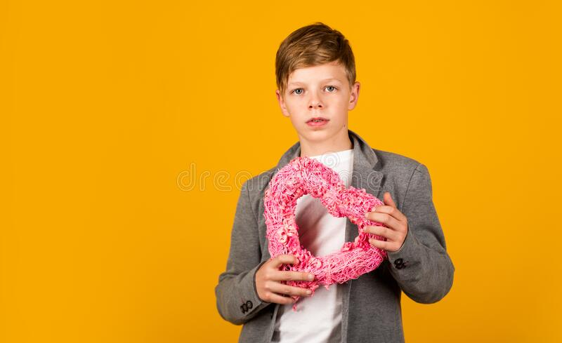 Valentines Day is here. Valentine boy yellow background. Small child hold valentines heart. Love symbol. Valentines royalty free stock photography