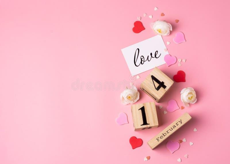 Valentines Day-konceptet Den 14 februari, träkalender, hälsningskort med påskriven kärlek, rosa och röda hjärtan royaltyfri foto