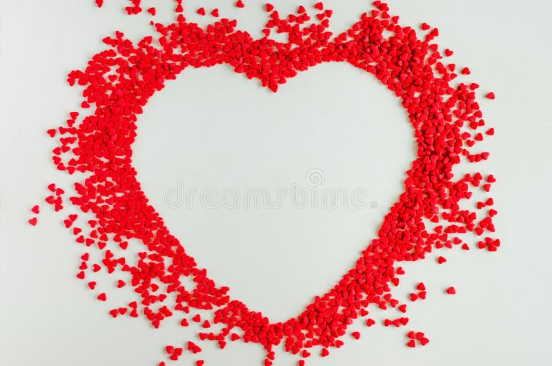 Valentines day love background. Red sugar hearts in the shape of a big heart. Creeting card for Valentines Day. Copy space, top view. Horizontal orientation stock image