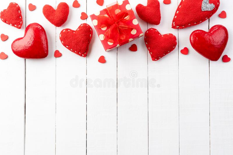 Valentines day and love concept. handmade red hearts with red gift box. On white wooden board stock photos