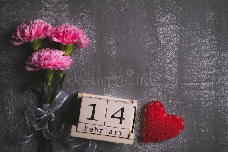 Valentines day and love concept. Pink carnation flower with February 14 text on wooden block calendar and red heart and on gray royalty free stock image