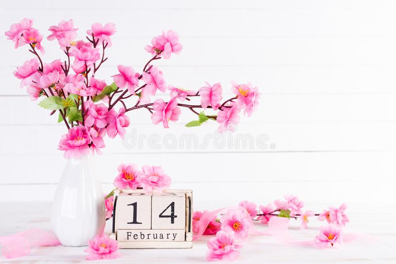Valentines day and love concept. Pink Plum Peach Blossom in vase with February 14 text on wooden block calendar on white wooden royalty free stock image
