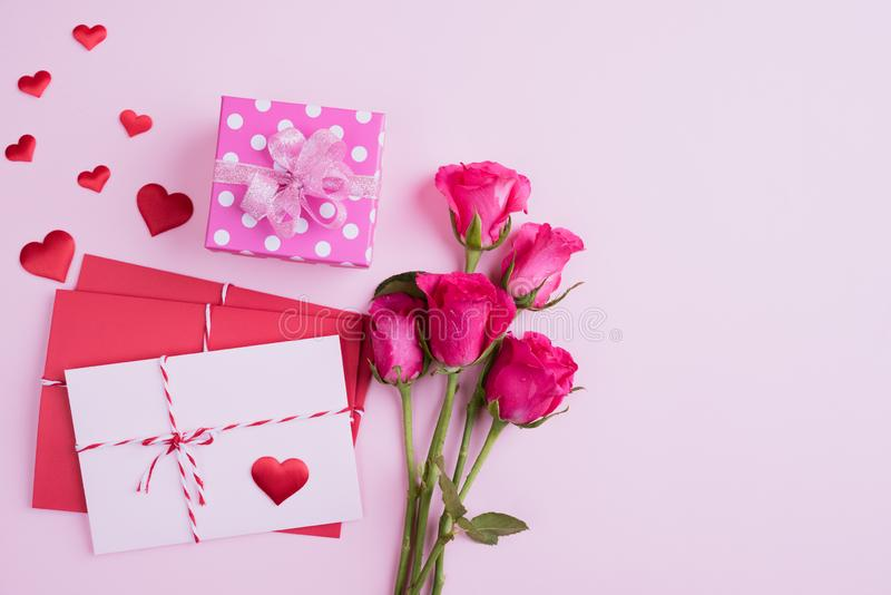 Valentines day and love concept. Pink roses, gift box with red heart and red pink letter cover on pink background stock image