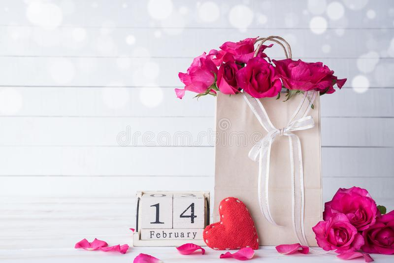 Valentines day and love concept. Pink roses in paper bag with February 14 text on wooden block calendar on white wooden background stock photo