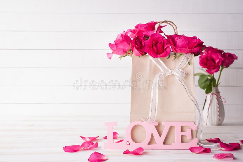 Valentines day and love concept. Pink roses in paper bag with Wooden letters forming word LOVE written on white wooden background royalty free stock images