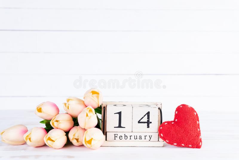 Valentines day and love concept. Pink tulips in vase with handmade red heart and February 14 text on wooden block on white wooden royalty free stock images