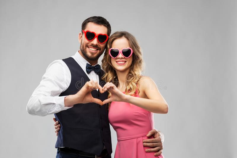 Couple in sunglasses making hand heart gesture. Valentines day, love and people concept - happy couple in heart-shaped sunglasses making hand heart gesture over royalty free stock image