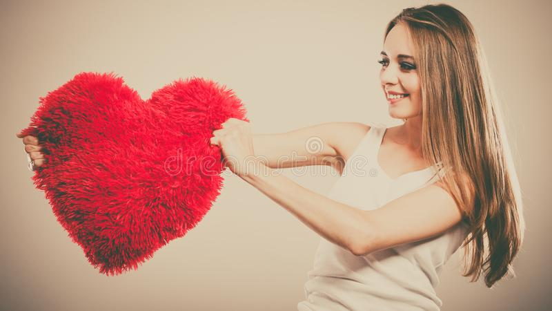 Woman holding heart shaped pillow love symbol stock photo