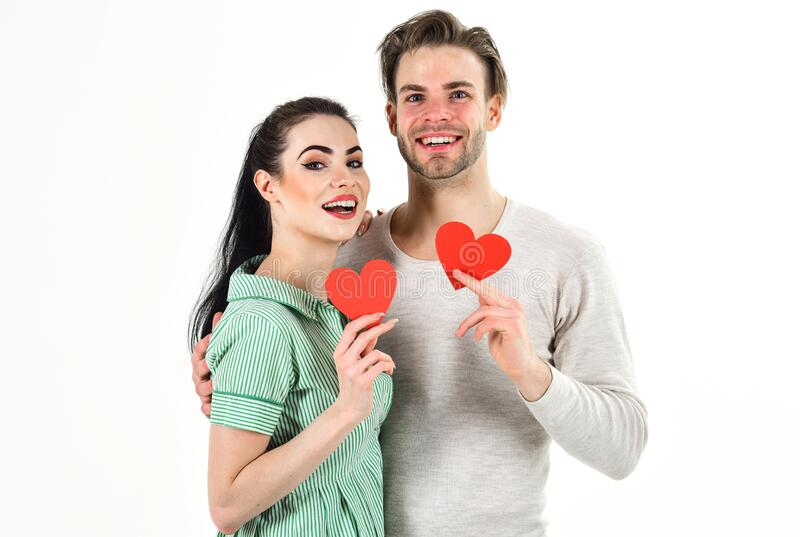 Valentines day and love. Romantic feelings concept. Man and woman couple in love hold red heart card on white background stock photo