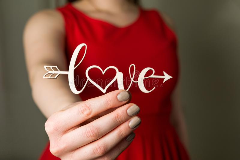 Valentines day love sign, beautiful woman in red dress holding love cupid arrow in hand,close up royalty free stock photo