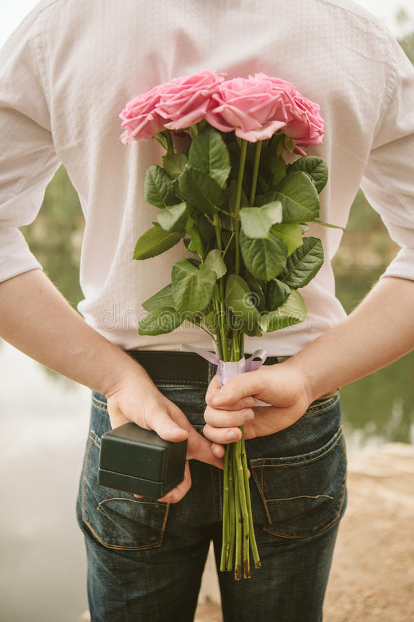 Valentines day. Man hiding behind a bouquet of flowers. Proposal scene stock image