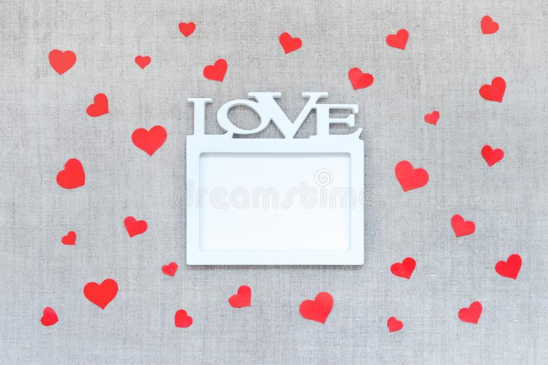 Valentines Day mockup with white frame with word LOVE and many red hearts on linen fabric background. Valentine Day, love, stock image
