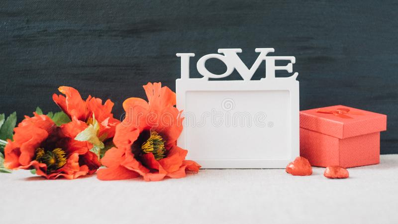 Valentines Day mockup with white frame with word LOVE, red poppies flowers and gift box on fabric and black background. Valentine. Day, love, romance, dating royalty free stock photos