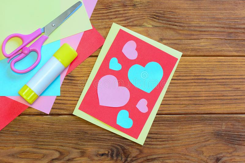 Valentines day or Mothers day paper greeting card with pink and blue hearts. Scissors, glue stick, colored paper sheets set. Paper projects. Simple paper stock images
