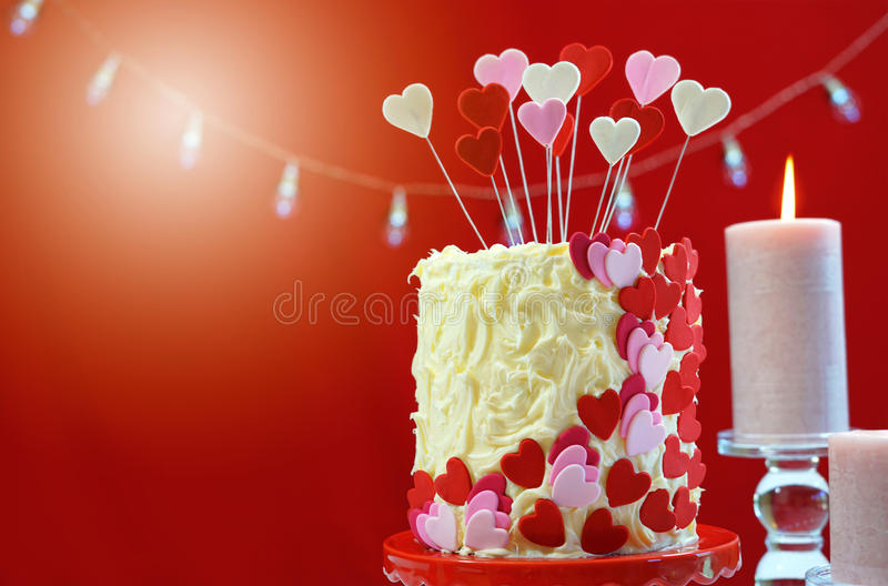 Valentines Day party table with showstopper hearts cake. Beautiful St Valentines Day party table with showstopper red, white and pink hearts double layer cake royalty free stock photos
