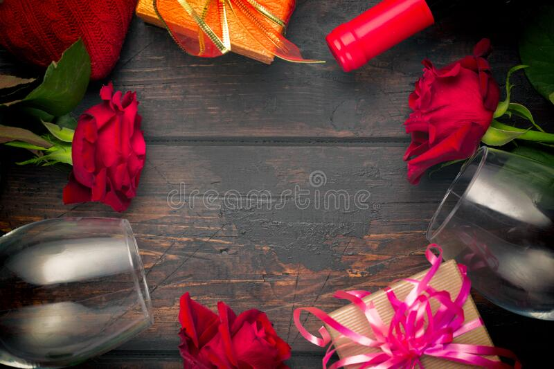 Valentines day romantic greeting card. Red rose flowers, wine bottle, two glasses and gift boxes on wooden table. Free space royalty free stock photos