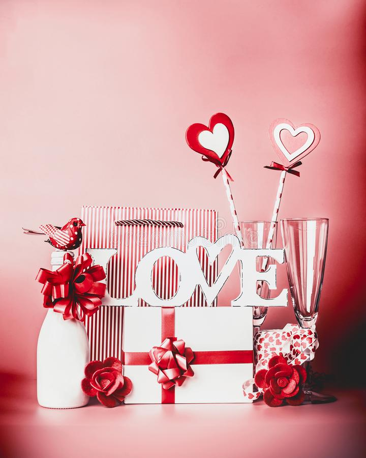 Valentines day romantic still life with word Love and greeting setting: champagne , gift box, ribbon, hearts and decoration at red royalty free stock photography