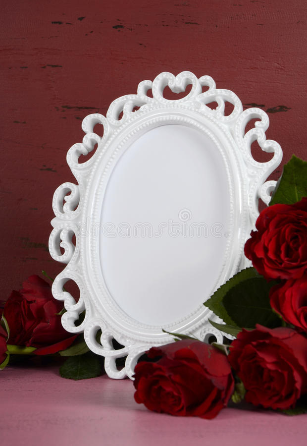 Valentines Day romantic vintage style white photo frame. Happy Valentines Day romantic vintage style white photo frame against red and pink rustic wood royalty free stock photo