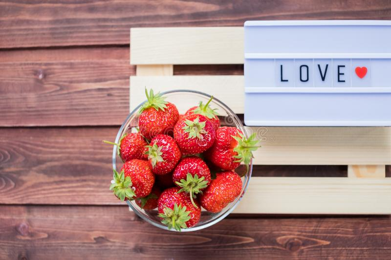 Valentines day, sweets and confectionery concept .word love made on light box and strawberry over wooden boards stock images