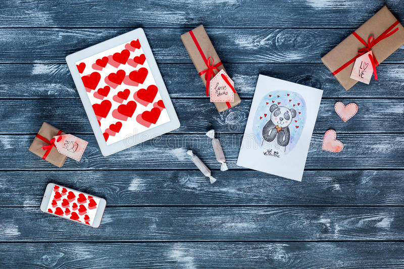 Valentines Day Symbols on Dark Wood Background. Valentines Day Items Gifts wrapped beige Color Paper and tied up with red Ribbon Gift Boxes of different Size and royalty free stock photos