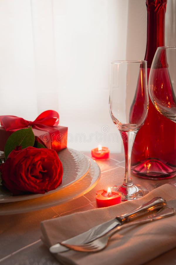 Valentines day table place setting with red roses and champagne. Invitation for a date royalty free stock images