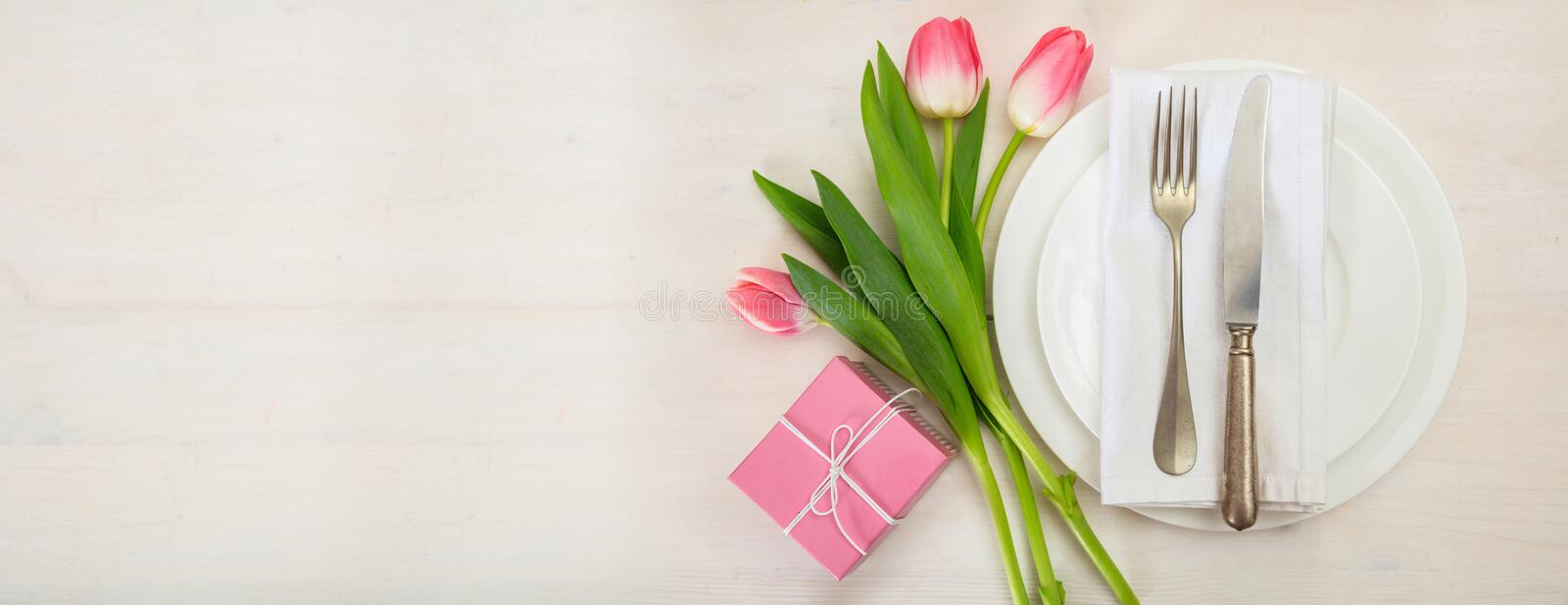 Valentines day table setting with pink tulips and a gift on white wooden background. Top view, copy space, banner royalty free stock images