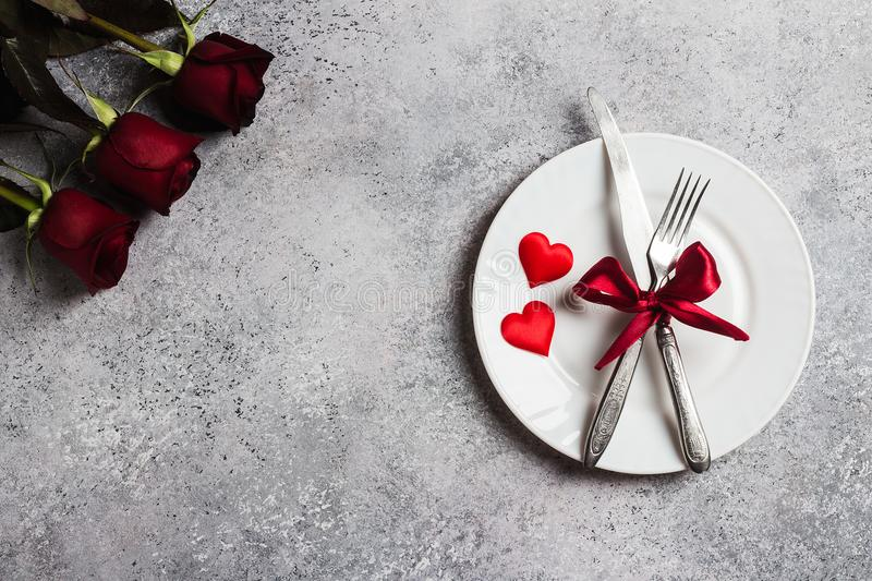 Valentines day table setting romantic dinner marry me wedding engagement. With red rose gift and plate fork knife on grey background with copyspace. Love flower stock photos