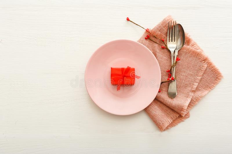 Valentines Day table setting on a white wooden table. Dinner meal in restaurant at Valentine Day.Present gift on pink plate. royalty free stock image