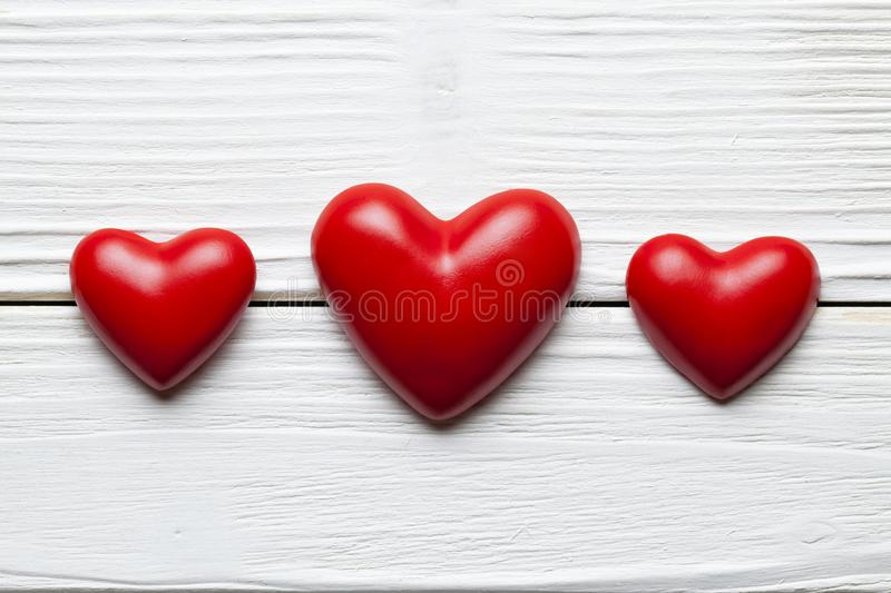 Valentines Day - Three red hearts on white planks stock images