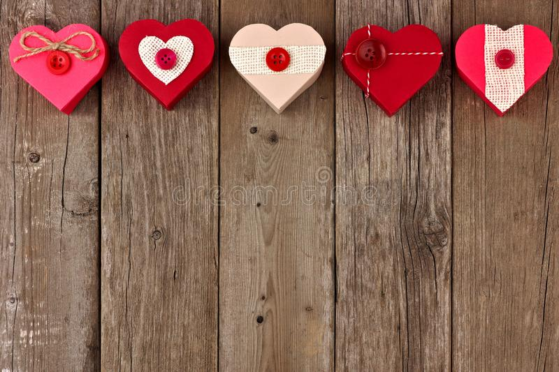 Valentines Day top border of red heart-shaped gifts over wood. Valentines Day top border of heart shaped gift boxes with red and burlap trim over wood stock image