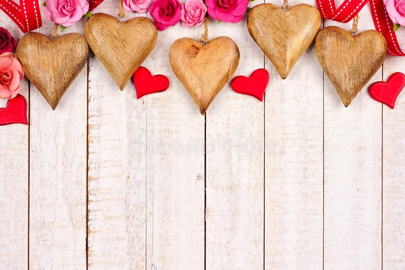 Valentines Day top border of wood hearts and paper roses against white wood stock image